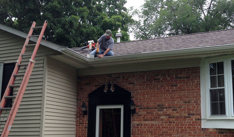 Man installing new gutters on house exterior
